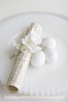 An Easter dinner blessing is scrolled, embellished with apple blossoms and placed at each setting.