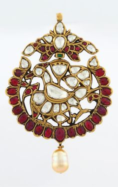 A DIAMOND AND RUBY PENDANT          Of openwork design, featuring a stylized bird, kundan-set with table-cut 'polki' diamonds, to a ruby-set surround, a similarly set surmount of foliate design, and suspending a single pearl, weighing approximately 6.00 carats, with a total diamond weight of approximately 12.50 carats, and a total ruby weight of approximately 8.50 carats, , mounted in gold.