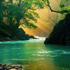 Love serene beauty.  Water.  Trees.  Rays of sun like a radiant rainbow.  Smooth rocks beneath the cool surface.