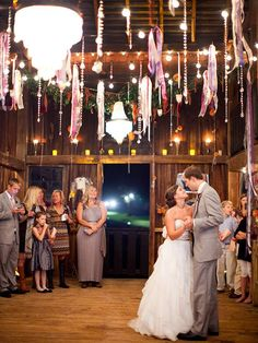 Utilize the rafters at a barn venue by draping crystals, twinkle lights or colorful ribbons as DIY rustic wedding decor.