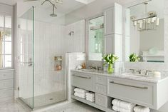bathroom with light grey double vanity, marble back splash, glass shower with white & grey tiled shower surround