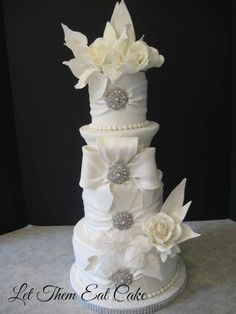 White Draped  wedding  cake with fondant and roses, pearls  and brooches