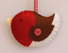 A wonderful Christmas Robin, just ready to be hung on the tree. Finished off with red gingham ribbon and a spotty button. Size approx: 10 cm x cm (not including ribbon hanger) If you purchase all 3 christmas decorations, you will only pay the stan. Bird Christmas Ornaments, Felt Christmas Decorations, Felt Ornaments, How To Make Ornaments, Christmas Sewing, Christmas Projects, Holiday Crafts, Christmas Ideas, Felt Projects