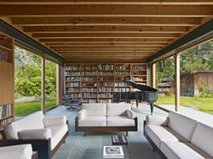 Living Room, Modern Style Living Room Ideas Also Grand Piano Plus Eames Lounge Chaise Chair With Huge Bookshelve And Glass Coffee Table Also Green Garden Designs Glass Window: Modern Living Room Design