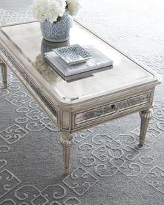 """Dresden"" Mirrored Coffee Table from Neiman Marcus: ""This mirrored table is wonderful because not only does it reflect light to take up less visual space, but the antiqued finish accents my 'Marie Antoinette Shabby Chic on Crack' design style perfectly. I'd love to put some great books and a floral arrangement on it."""