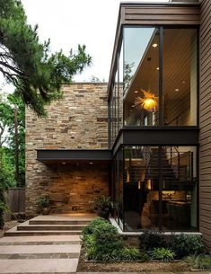 maison moderne qui bénéficie d'une façade en verre et métal et un pan de mur décoré de pierre de parement extérieur
