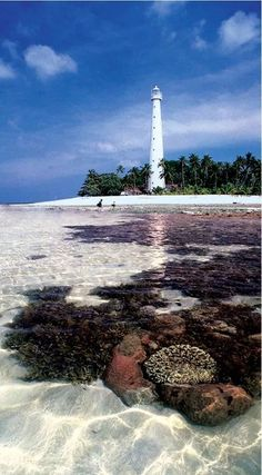 Lighthouse on Lengkuas Island a small island located in the east of the island of Belitung, Indonesia. You can climb inside this lighthouse but you must be prepared to climb 12 floors if you want to enjoy the beauty of the island from the top of the lighthouse.  There is a window on every floor where you can stop and admire the beauty around you.  Built in 1882 by the Dutch Colony Government this old lighthouse is still a guiding light.