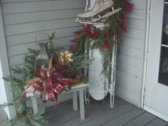 Christmas on the old porch; sled, lantern, pinecones, old iceskates