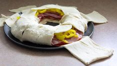 Crescent dough in a circle wrapped around ham, salami, peppers and cheese filling