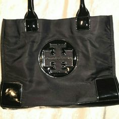 """Tory Burch black  ELLA  tote FLAWS : inside at bottom crease is a dark line stain and some pen marks..if picky I'd say a 7. If not I'd give  a 8.5  Measurements are 13""""L  X 9""""H  X 5""""D and a 7""""strap drop  (Note: When unsnapped on sides it expands to 17""""L .) .inside has one zip pocket and two open pockets with a magnetic snap closure. Logo on front. Double top handles. Outside looks great.offers are welcome thru offer button only plz Tory Burch Bags Totes"""