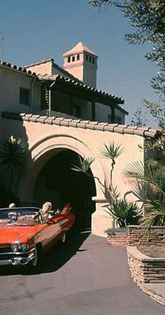 Jayne Mansfield in the driveway of her beverly hills home in her 1959, cadillac with one of her kids.