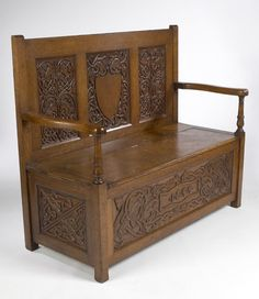ATTRIBUTED TO ALEXANDER RITCHIE  CELTIC REVIVAL OAK HALL SETTLE, DATED 1899  the rectangular back carved with three panels of elaborately carved Celtic knotwork and mythical beasts, above a solid hinged seat and open arms raised above similar carved panels on three sides centred by a cartouche dated 1899,  128cm wide