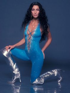 Cher during the 1970s disco era wearing a blue catsuit and silver boots