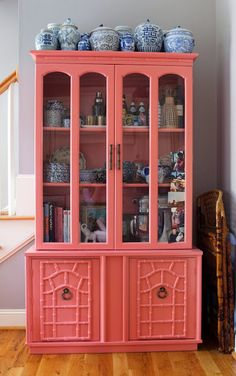 Coral painted bamboo cabinet with ginger jars.