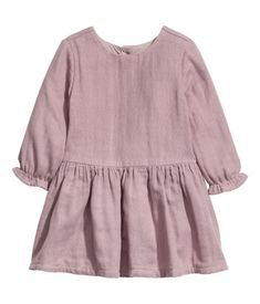 Heather purple. BABY EXCLUSIVE/CONSCIOUS. Dress in soft organic cotton with buttons at back and long sleeves with ruffle trim. Seam at waist and flared