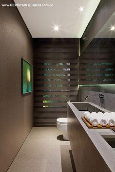 Espelho e bancada de mármore acompanham a extensão da parede do lavabo com papel de parede escuro e luminotécnica intimista. O quadro é de Alberto Oliveira