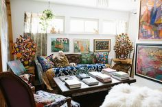 "It's difficult to choose the star in the loft, where vintage African sculpture resides alongside Aldridge's vast collection of artwork and a 1950s sofa—only $45!—reupholstered in a blue-and-white ikat fabric. ""This room tends to be a catchall,"" she says. ""In spite of that, it's also everyone's favorite place to gather."" To switch things up, Aldridge will often toss a few textiles over the couch, which has the added benefit of keeping her pups from doing any permanent damage. Behind the sofa…"