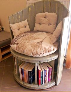 Reading chair made from an old cable spool and slat wood back. Spool has been divided off underneath to serve as book storage.