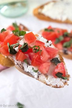 Tomato and Basil Crostini with Whipped Feta - Crunchy crostini with zesty, tangy, creamy whipped feta, then topped with diced tomatoes and garnished with fresh basil.