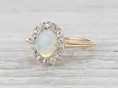 Vintage Victorian ring made in 18k yellow gold and centered with an approximately .75 carat cabochon opal. Accented with old mine diamonds weighing approximately .40 carats total. Circa 1890. Nothing beats a beautiful opal set with a halo of diamonds! The band is delicate and thin making this ring very comfortable and light on the finger. Diamond and gold mining has caused devastation in areas such as Africa, wreaking havoc on delicate ecosystems and communities. Choosing to go vintage…