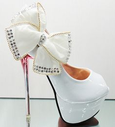 White stiletto ultra high heeled shoes with hidden platform, pointed toe and round vamp.  Trending style feminine wedding shoes have a white bow with silver accent on the side.