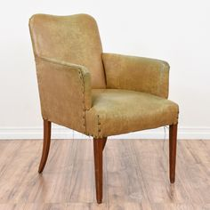 This country chic armchair is upholstered in a durable vinyl with a distressed faux leather finish in light tan. This chair is in great condition with light cherry legs, nailhead trim and a curved back. Comfortable chair perfect for a reading room! #country #chairs #armchair #sandiegovintage #vintagefurniture