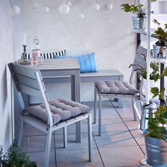 Terraza pequeña con mesa gris, banco y sillas con cojines de asiento