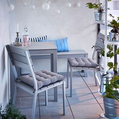 A small balcony with grey table, bench and chairs with seat cushions