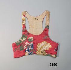 """Stora Tuna, Dalarna, ca 1820-40. Fabric: 18th c. silk """"Livstycke med litet skört, sytt av ett återbrukat sidenbrokadtyg från 1700-talet med stort blommönster i grönt, blått, gult, vitt och ljusbrunt på starkröd botten. Skuret i 2 framstycken/sidstycken och 2 ryggstycken med många materialskarvar. På axlarna iskarvat med ett beigemönstrat siden. Små infällda skörtkilar i sidorna, skörtflikarna bak är sammansydda och styvade och infodrade med rödbottnad kattun samt ett annat småmönstrat…"""