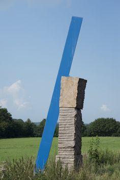 #Büdelsdorf Drei übereinander geschichtete Granit-Blöcke werden flankiert bzw. hoch überragt von einem langen flachen blauen Eisen. Der Berührungspunkt von Stein und Eisen ist schmal und fragil und symbolisier...