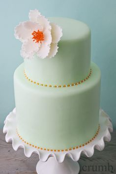 My kind of cake.  Beautiful colour, small with gold piping, but I'd put some coral onto it in a different way than the middle of that flower.  ᘡηᘠ