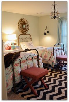 Big girl room: brass twin beds, mirror over bed, shared nightstand, x bench at foot, and chandelier.