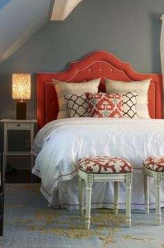 Beautiful red gray blue bedroom design with blue & gray walls paint color, red velvet tufted headboard with white piping, white hotel bedding with red stitching, blue & gold rug, white & black moorish tiles pillows, ivory & gray silk striped pillows and ivory french stools with red coral linen upholstery. just the color