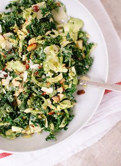 A simple, filling kale + brussels sprouts salad. || Thinly sliced brussels sprouts and toasted slivered almonds lend slaw-like crunch, while parmesan and miso contribute savoriness.