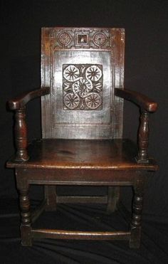 """A EARLY 17TH CENTURY SALISBURY OAK WAINSCOT ARMCHAIR.    WITH DEEP CARVED TOP RAIL AND A RECTANGULAR ROSETTE CARVED BACK PANEL, WITH UNUSUAL SHAPED ARMS AND SEAT.SEE V. CHINNERY """"OAK FURNITURE THE BRITISH TRADITION"""" FOR SEVERAL EXAMPLES. MINOR REPAIR TO ONE ARM AND BACK FEET. GOOD COLOUR AND PATINATION. 41"""" HIGH X 26"""" WIDE X 18"""" DEEP."""