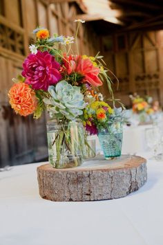 Take a tree stump and saw off a small slice. Add a mason jar filled with flowers, and you have a perfect centerpiece for your tables! #countrywedding #westernwedding #reception #flowers #centerpiece