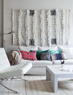 Love the texture in this room. A great example of white on white done right! Awesome idea of adding the rug add artwork to the wall above the sofa!!