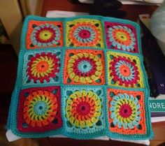 This variation on the ever-popular granny square features a circular centre motif. Made up in bright colours, this cushion cover has a fiesta feel and would look equally at home in a camper van or caravan, or in your living room. We've added a vibrant green fabric backing to make the yarn shades really sing.