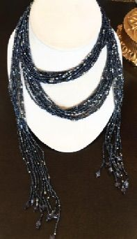 "Forty inches of chic. Blue beaded boa is 9 stands of indigo beads,with silver interspersed for extra bling, wear, wrap and drape  any way you please. 40"" long."