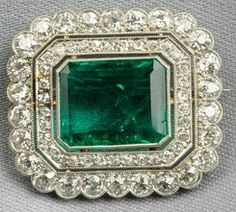 Art Deco emerald and diamond brooch, bezel-set with an emerald-cut emerald, framed by old European and old mine-cut diamonds, platinum mount with millegrain accents.
