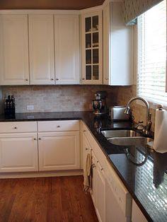 Light cabinets; travertine/ stone backsplash; black granite countertops