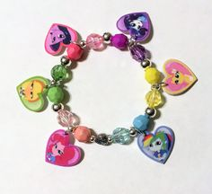 This My Little Pony Equestria Girls Mane 6 Charm bracelet will win her heart!  This bracelet is strung on strong stretch jewelry cord to a length of 6 inches with beautiful colored opaque and translucent faceted beads, accented with SILVER PLATED metal beads and a metal heart bead. The handmade single sided plastic charms feature the Mane 6 Equestria Girls in a heart shape. This bracelet will surely find a place in the heart of your My Little Pony Equestria Girls fan! This bracelet will make…