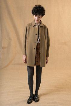 Manteau à manche raglan, boutonnage sous patte et poches passepoilées.
