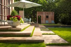 To help soften the clean geometric lines of the stone steps, grass is planted at the risers. Large stone urns are full of beautiful plantings, while contemporary yet comfortable furniture overlooks the negative-edge pool. Best Patio Umbrella, Patio Umbrellas, Rectangular Planters, Rectangular Pool, Modern Backyard, Large Backyard, Landscape Architecture, Landscape Design, Ideas De Piscina