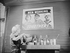 Balloon room worker mixing cement is reminded of the importance of her task by OPM (Office of Personnel Management) poster hanging on balloon room wall at the Goodyear plant in Akron, Ohio, 1941.