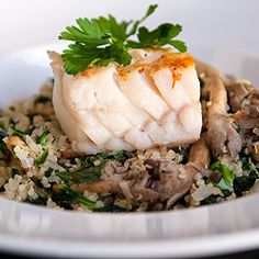 Quinoa with sautéed mushrooms and kale served with pan-seared cod.