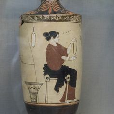 Domestic Scene. A woman in a long sleeved chiton, with himation around her legs, earrings, bracelets, hair looped up, with rows of curls over forehead, seated on a diphros to right, holding up with both hands a hoop, which she grasps with thumb and finger of the left hand above and of right below. On right hangs from the upper border a saccos; on left, from an oblong object, an alabastron with cords; behind her, a large basket. In the field near the head, ΚAΛE. Late stage of severe style…