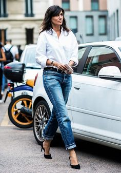 Emmanuelle Alt wearing a white shirt tucked in classic jeans with a black jean belt.