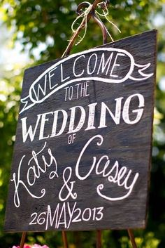 farm wedding ideas: white lettering on a panel of darkened wood for welcome sign.