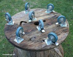 hjul med lås skruet under en stor kabeltromle der skal bruges til bord på en terrasse